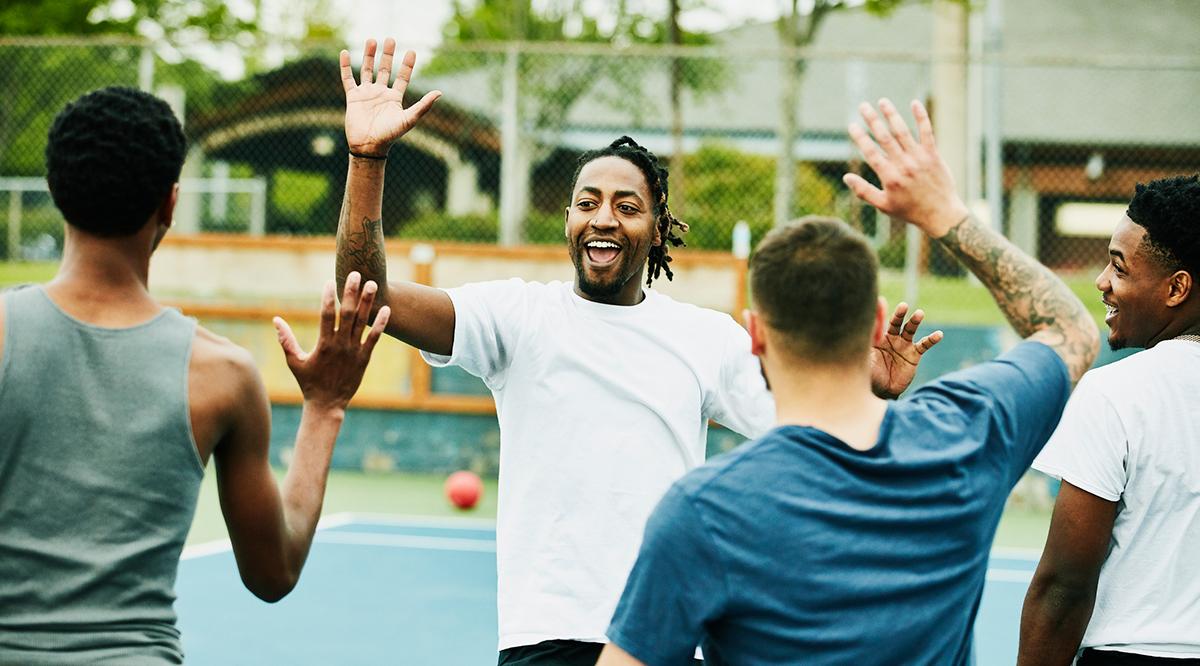Smiling man high fiving teammates after winning dodgeball game