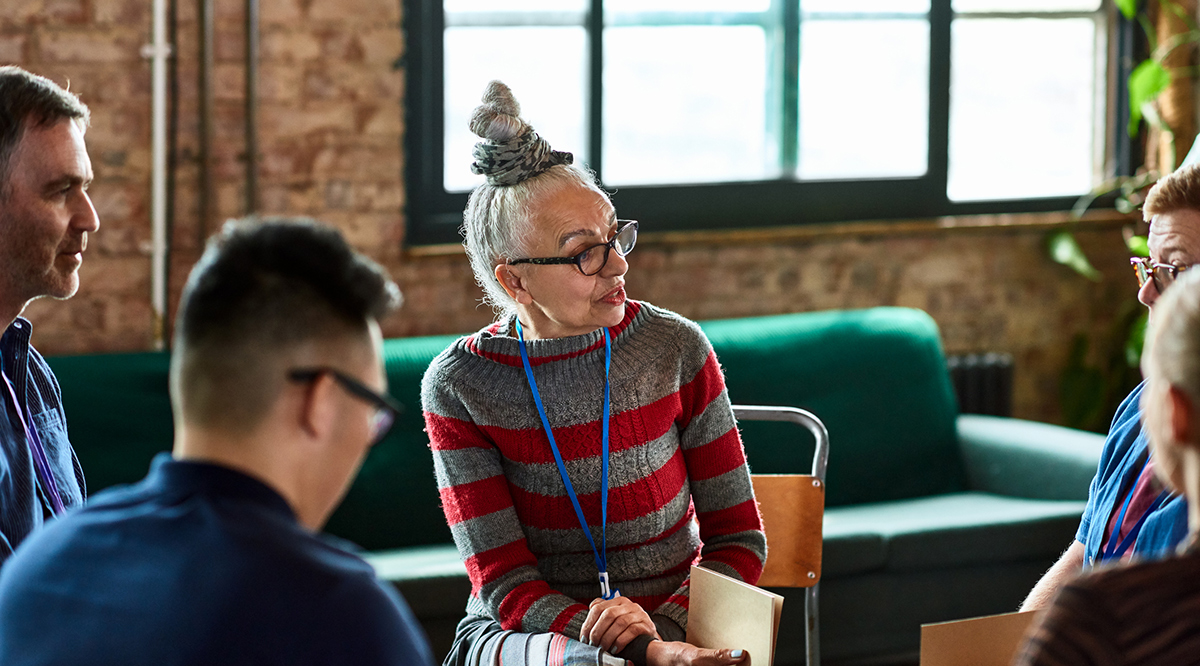 Senior woman talking to small group in office training session